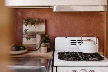 close up of small stove, kitchen knickknacks and teapot