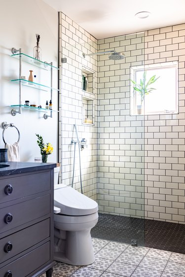 bathroom shower with white subway tile, blue bathroom vanity with sink, toilet and over-the-toilet storage