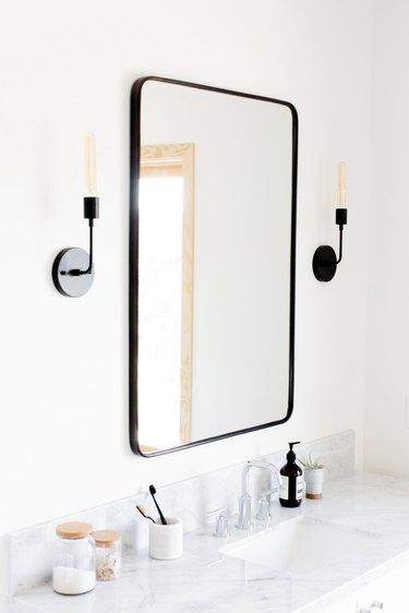 Faux candlestick style bathroom vanity lighting ideas over marble vanity