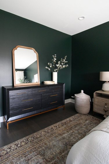 Traditional bedroom with green walls and classic black dresser