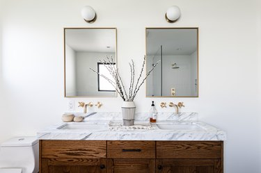 bathroom vanity cabinet and double sink, two rectangular mirrors with gold trim and two lights