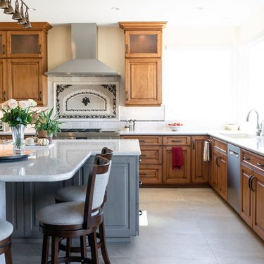 wood cabinets in traditional kitchen with patterned travertine backsplash