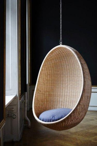 Egg shaped swing green walls wood floor