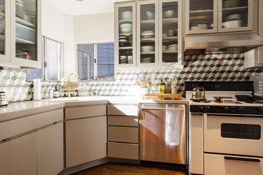 kitchen with glass-fronted cabinets, stove, corner-sink and interesting backsplash
