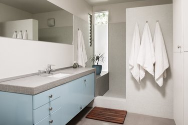 blue and grey bathroom vanity cabinet with sink, walk-in shower and three towels on hooks