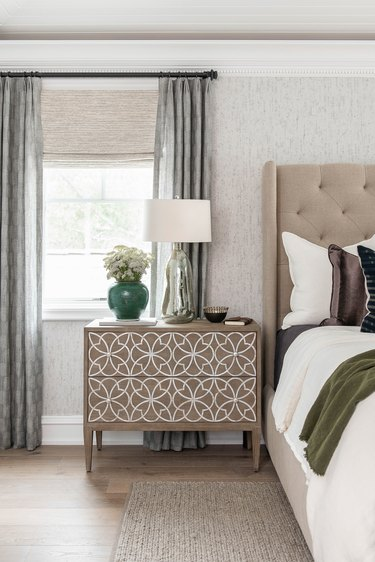 Traditional bedroom with patterned dresser and upholstered headboard