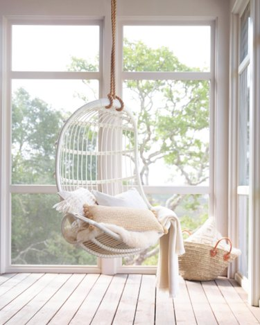 Sun porch, white pillows, large windows, hanging rattan white chair