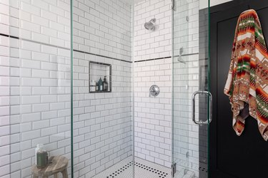 bathroom with standing shower with subway tile wall tiles, black door and decorative towel draped over it