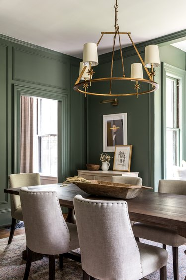green traditional dining room with wooden table and brass chandelier