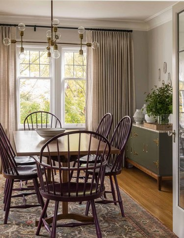 traditional dining room with purple Windsor-style chairs and green storage cabinet