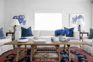 patterned family room carpet ideas with vintage rug, white couch, and blue pillows
