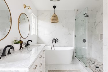 white bathroom, quartz countertop on white vanity, large white soaking tub, glass shower, two round mirrors with gold trim