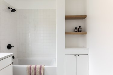 white tile, white combination tub and shower, built-in wood shelves