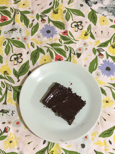 patterned tea towel with plate with chocolate cake on top