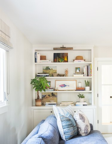 living room shelving idea in white space with blue sofa