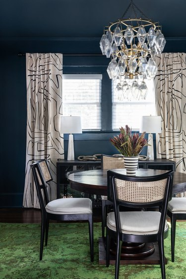 blue traditional dining room with green rug and chandelier