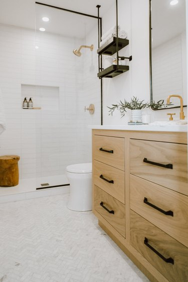 bathroom towel storage idea in white bathroom with walk in shower