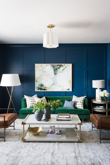 blue living room idea with green sofa and leather accent chairs