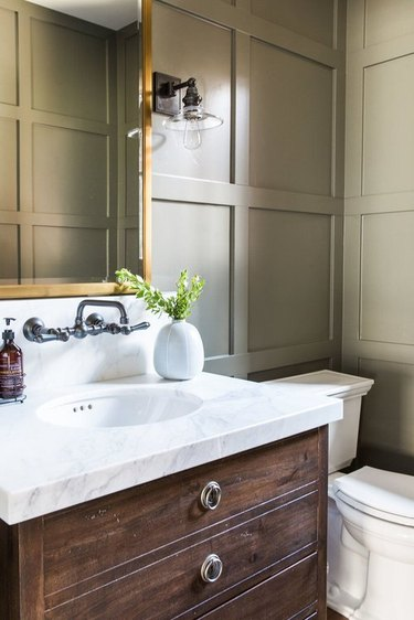 Taupe color in bathroom with wall panels and gold vanity mirror
