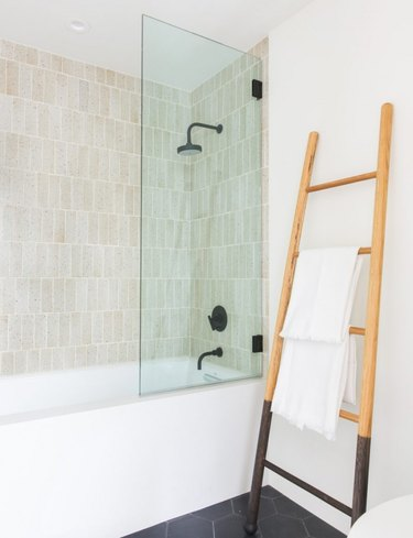 bathroom towel storage idea with ladder leaning against wall next to partial glass shower enclosure