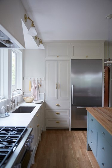 Taupe colors in kitchen with blue island and wood floors