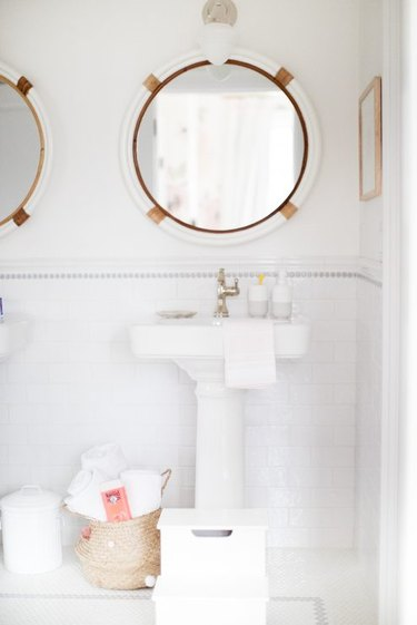 bathroom towel storage idea in white bathroom with round mirrors and pedestal sinks