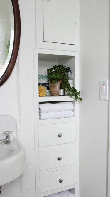 bathroom towel storage idea with round mirror and bult-in cabinet storage