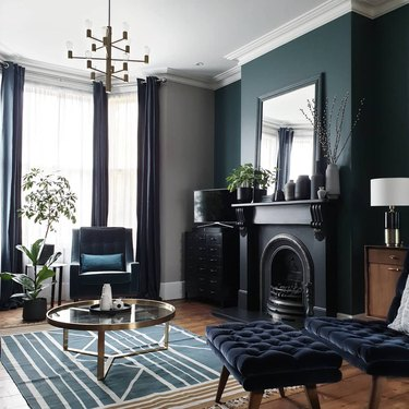 Darkly-colored blue living room idea with floor to ceiling drapery and black fireplace