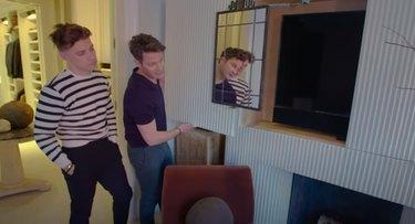 two figures standing near TV hidden behind a panel