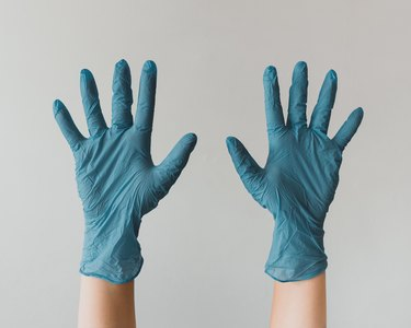 person wearing blue latex gloves and lifting their hands in the air
