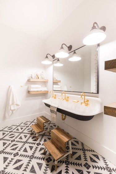 bathroom towel storage idea in white and black bathroom with patterned floor and trough sink