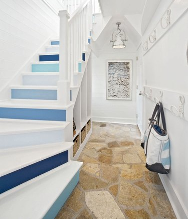 blue and white ombre stair wallpaper on risers of white staircase