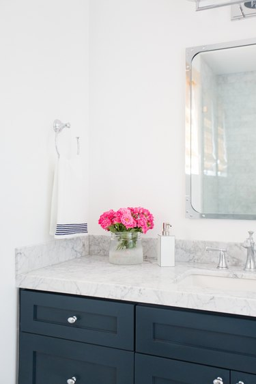 guest bathroom idea with fresh-cut pink flowers in a clear glass vase on a clean marble bathroom countertop