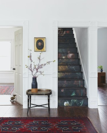 white entry with moody stairs wallpaper on risers with wood treads