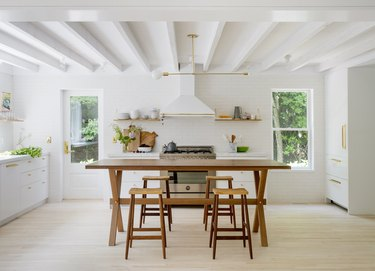 White kitchen design with rustic table and stools