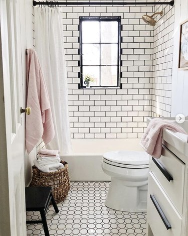 guest bathroom idea with a black and white tiled bathroom with a basket full of pink and white towels