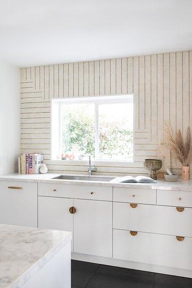 Art deco tile backsplash with brass inlaid details in modern white kitchen