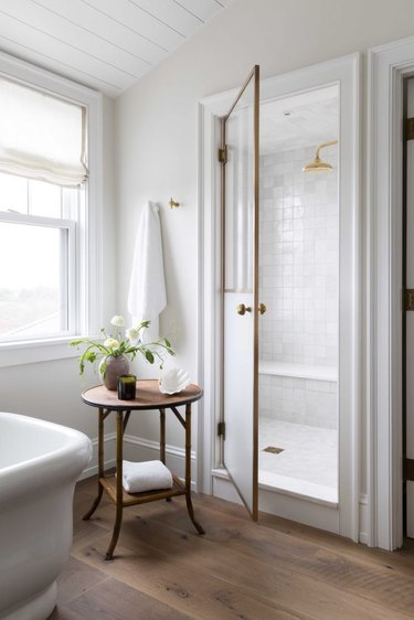 guest bathroom idea with a small round wooden table in a white bathroom with a pitched roof and large white-tiled walk-in shower