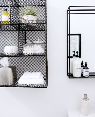 guest bathroom idea with cotton swabs, cotton balls, and white towels neatly organized on a black wire shelf hung on a white bathroom wall