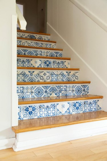white staircase with blue and white stairs wallpaper on risers