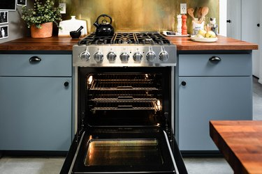 open stainless steel oven surrounded by light blue cabinets and wood countertops