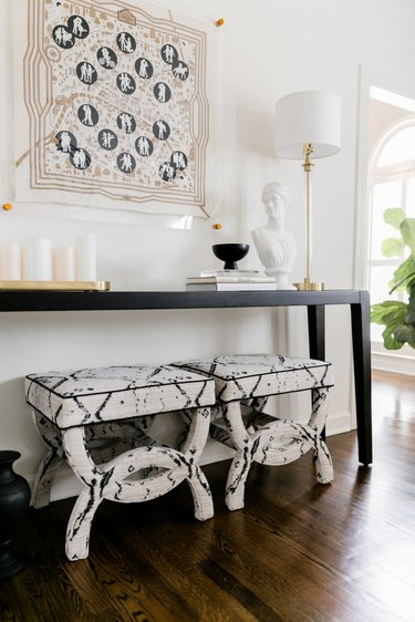 Traditional entryway table with upholstered stools and black and white decor