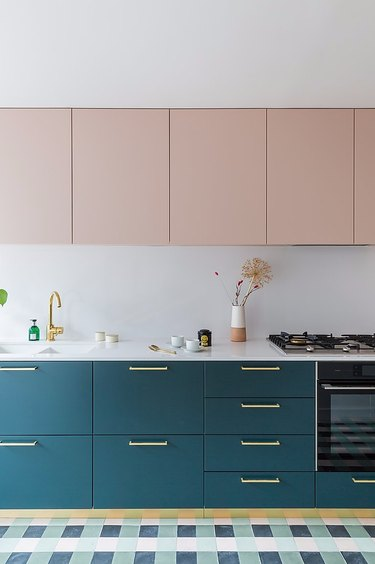 pale pink upper cabinets with teal color lower cabinets and white countertop