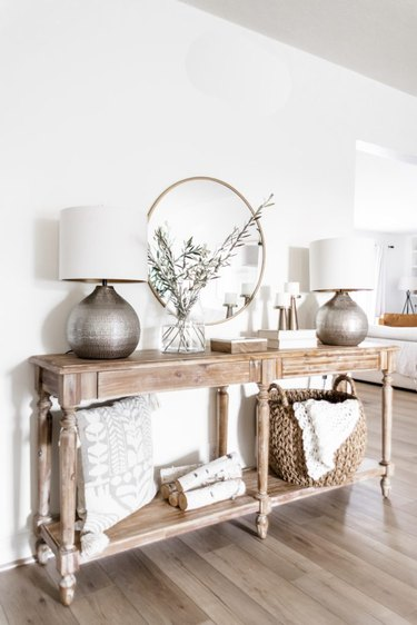 Traditional entryway table with round mirror and other traditional decor details