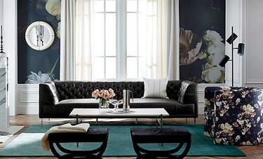 teal color ombre rug in living room with floral wallpaper and tufted sofa