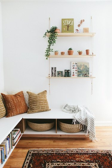 Living room storage ideas below corner seating and shelving on the wall