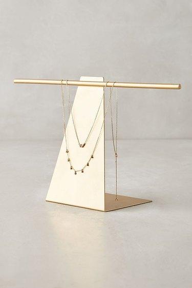 A triangular metronome-like jewelry stand.