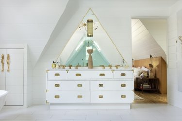 white apartment bathroom idea in A-frame space with brass details