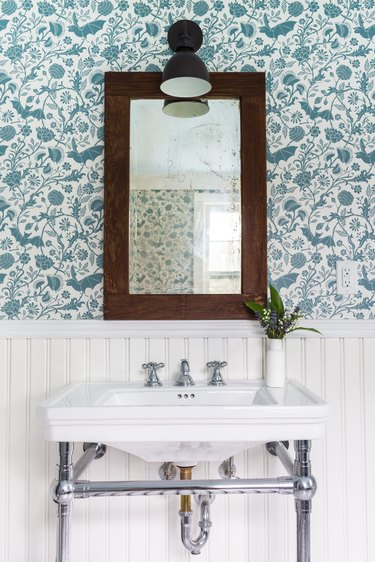 apartment bathroom idea with wainscoting and wallpaper and console sink