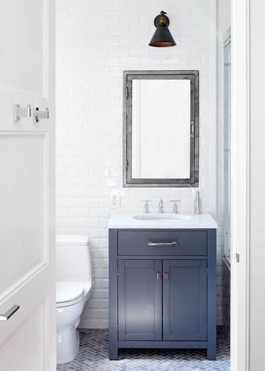 apartment bathroom idea with blue vanity and white walls